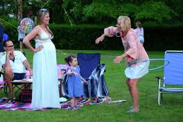 "Hunter Claire Carleton, 2, of Westport, watches as her grandma Glory Wojdyla plays with a hulahoop during Pequot Library's annual ""Potluck, Outdoor Concert & Campout,"" at the library in Southport, Conn., on Friday June 9, 2017. An outdoor concert with the Merwin Mountain Band started the evening off. A campfire was built for everyone to make smores and at twilight kids held a big pillow fight before retiring to their tents to camp out overnight."