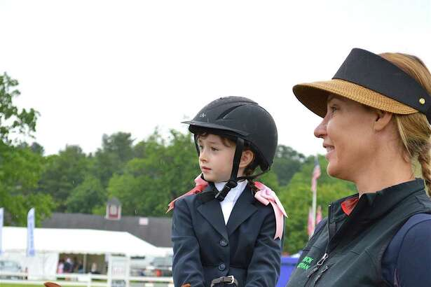 Isabelle Castellanos, 5, of New Canaan, guided by Juliana Starbuck of Ridgefield, at the Ox Ridge Hunt Club's June Horse Show, Saturday, June 17, 2017, in Darien, Conn.