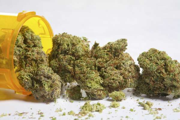 Marijuana buds coming out of pill bottle.
