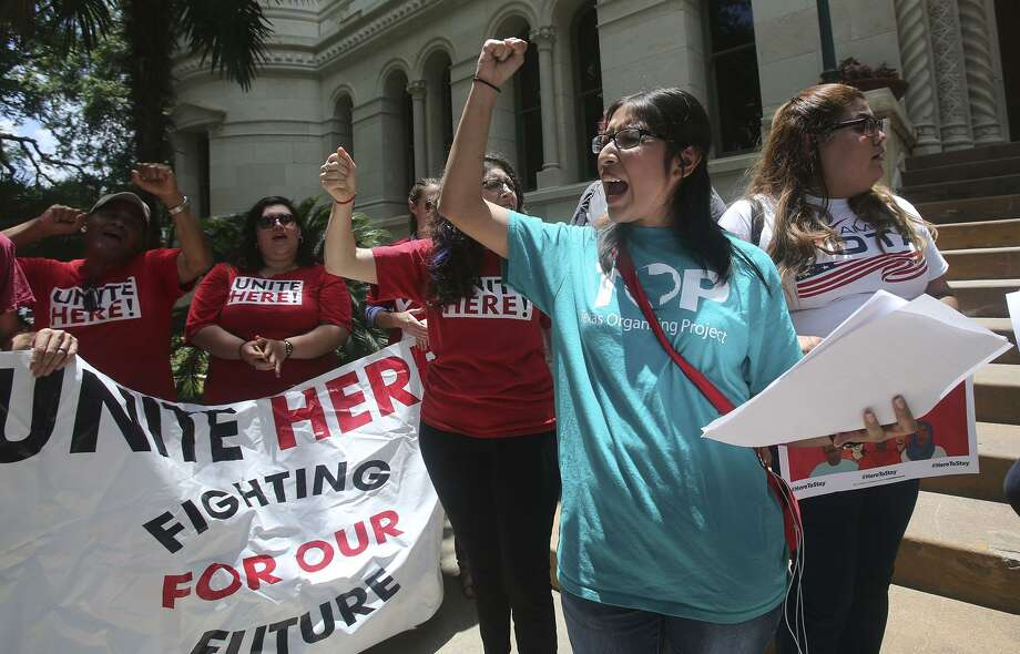 Jessica Azua (right, foreground, arm raised) leads a chant Thursday June 1, 2017 during an announcement made in front of city hall regarding a lawsuit over Senate Bill 4. Senate Bill 4 allows police officers to question a person's immigration status during a detainment. Photo: John Davenport, STAFF / San Antonio Express-News / ©John Davenport/San Antonio Express-News