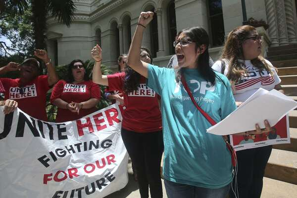 Jessica Azua (right, foreground, arm raised) leads a chant Thursday June 1, 2017 during an announcement made in front of city hall regarding a lawsuit over Senate Bill 4. Senate Bill 4 allows police officers to question a person's immigration status during a detainment.