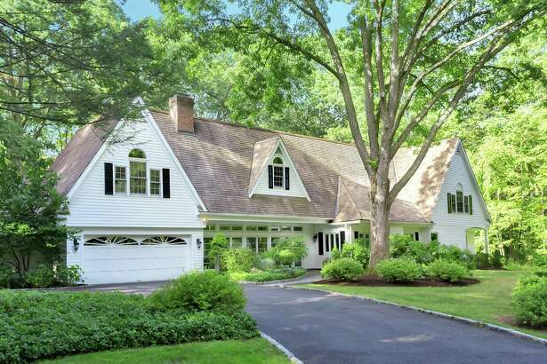 The colonial manor house at 25 Powder Horn Hill Road sits on a 2.79-acre level property in central Wilton, within walking distance of the New Haven Metro-North train station.