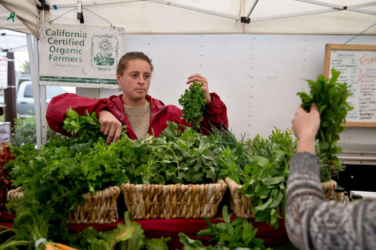 Jan Velilla helps a customer while working at the Full Belly Farm stand during The Ecology Center Farmers' Market in Berkeley, Calif., on Tuesday, April 1, 2014.