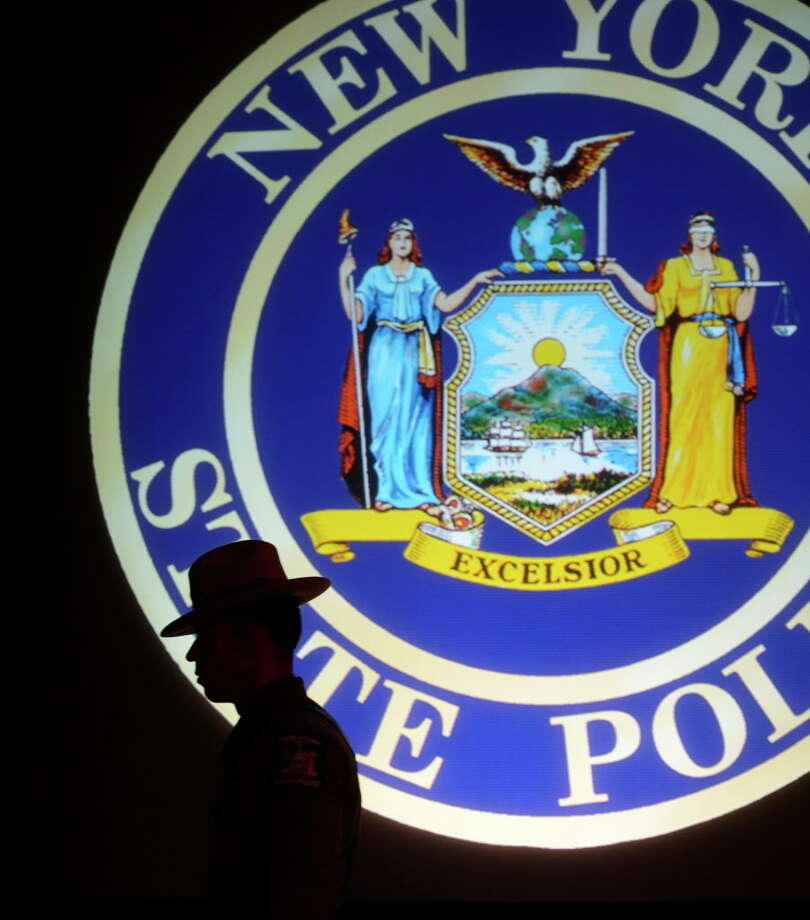 A trooper walks under the seal of the New York State Police after the  graduation ceremony of 199th class of the New York State Police was held in the Convention Center of the Empire State Plaza May 29, 2013,  in Albany, N.Y.   (Skip Dickstein/Times Union) Photo: SKIP DICKSTEIN / 00022574A