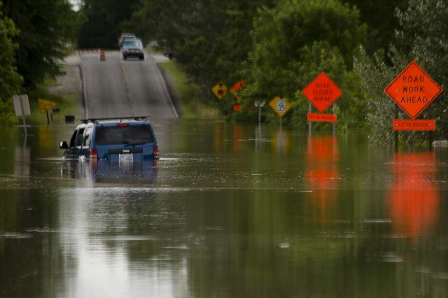 A vehicle is partially submerged in floodwater on N. Sturgeon Road north of Airport Road on Friday, June 23, 2017. Photo: (Katy Kildee/kkildee@mdn.net)