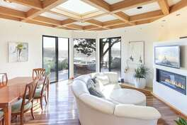 The living room at 239½ Cleveland Ave. in Mill Valley offers a gas fireplace and a pair of sliding glass doors leading outside.