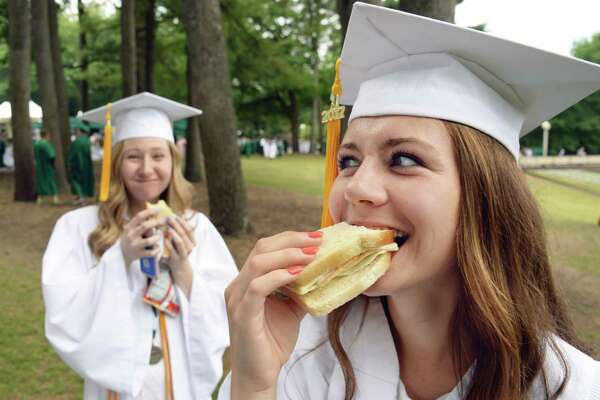 Kate Healy, left, and Kendra Harbinger take a little nourishment before Commencement exercises for Shenendehowa High School Class of 2017 at SPAC Friday June 23, 2017 in Saratoga Springs, NY.   (John Carl D'Annibale / Times Union)