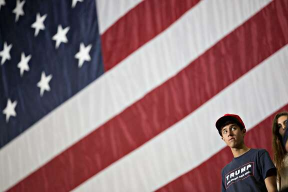 An attendee stands in front of a large American flag while waiting for the start of a rally with U.S. President Donald Trump in Cedar Rapids, Iowa, U.S., on Wednesday, June 21, 2017. Russia canceled talks with a top U.S. official to protest the latest sanctions punishing Russian companies and individuals over the conflict in Ukraine, in a fresh setback for Trump's bid to improve ties with President Vladimir Putin's government. Photographer: Daniel Acker/Bloomberg