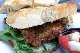 Crossroads Kitchen serves a fried chicken sandwich with pickled jalapeños, spinach and ranch dressing.