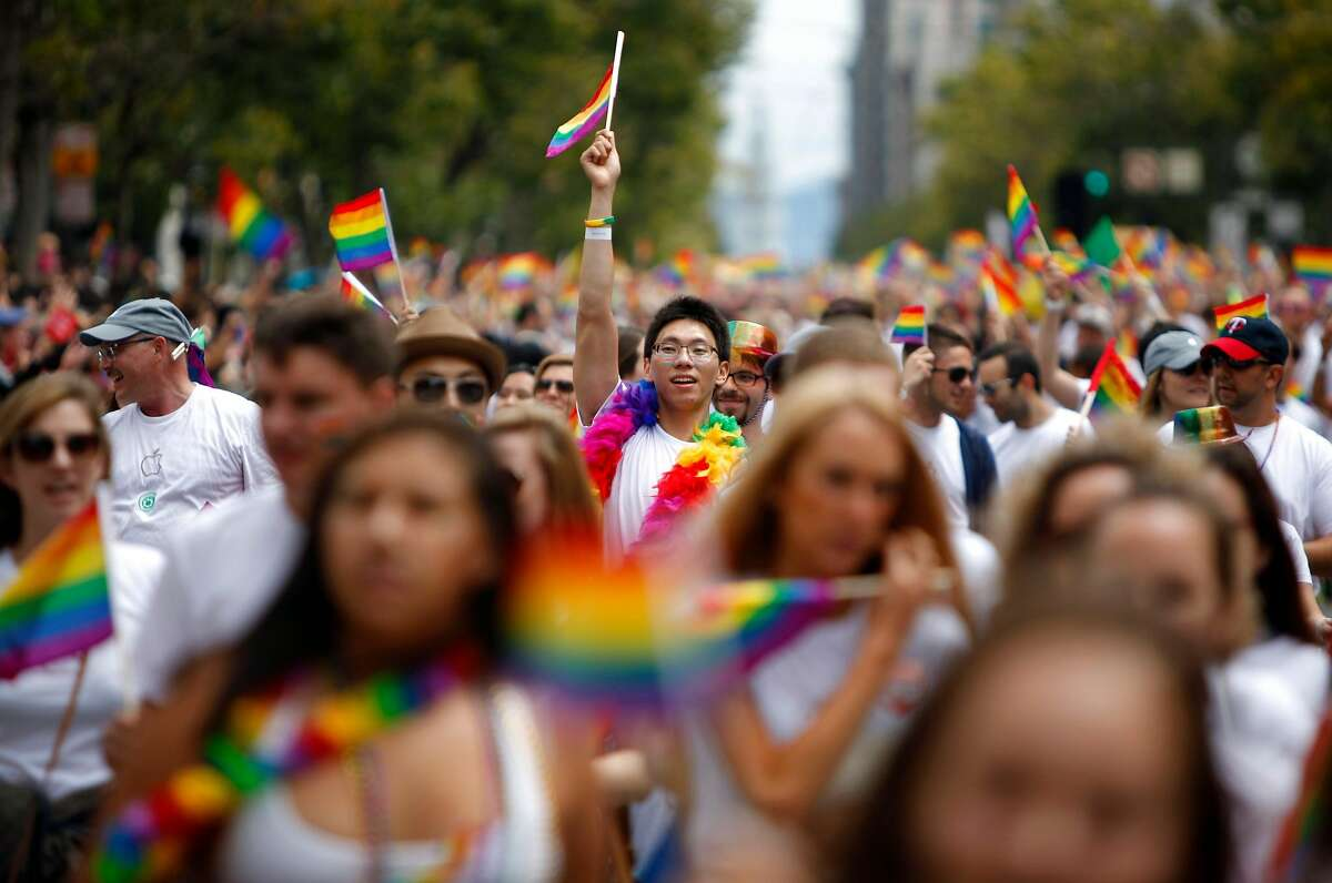Pride supporters of Apple cheer and raise their gay pride flags high as they make their way down Mark Street during the Pride Parade in San Francisco, California, on Sunday, June 28, 2015.