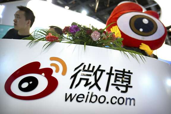 In this April 27, 2017 photo, staff members wait for visitors at a booth for Chinese microblogging website Sina Weibo at the Global Mobile Internet Conference (GMIC) in Beijing. Three popular Chinese internet services have been ordered Thursday, June 22, 2017, to stop streaming video after censors complained it contained improper comments about sensitive issues. The move prompted a sell-off in the U.S.-trade shares of Sina Corp. and its microblog service, Sina Weibo. (AP Photo/Mark Schiefelbein)