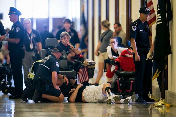 Protesters staging a �die-in� are removed from outside the office of Senate Majority Leader Mitch McConnell (R-Ky.) on Capitol Hill in Washington, June 22, 2017. McConnell took a major step Thursday toward repealing and replacing the Affordable Care Act, unveiling a bill that would make deep cuts to Medicaid and end the mandate that most Americans have health insurance. (Al Drago/The New York Times)