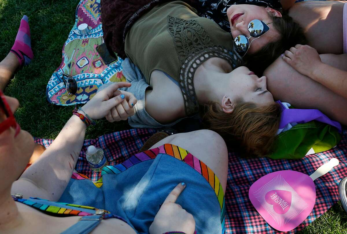 Clockwise from lower left, Bee Geiger, Emma Cushman, Violet Moyer and Alex Quiroz lounge together with friend Rach Pitts (not visible) before the start of the Trans March in Mission Dolores park June 23, 2017 in San Francisco, Calif. The annual march kicks off a weekend of Pride events held around the city.