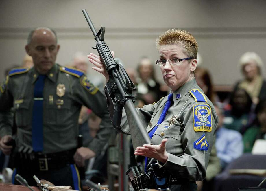 A state police detective holds up a Bushmaster AR-15 rifle, the make and model of gun used by Adam Lanza in the Sandy Hook School shooting. Photo: Jessica Hill / Associated Press / FR125654 AP