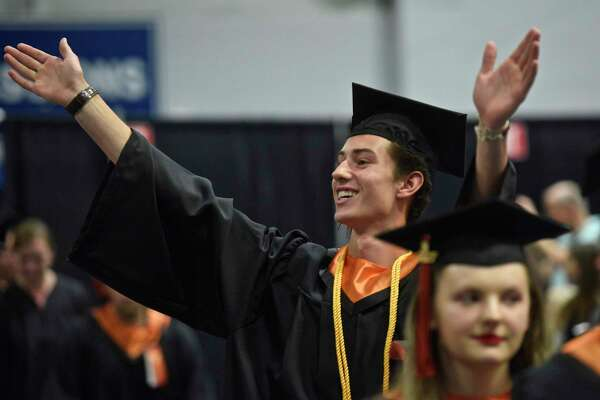 Jake Barrett waves to his family during the processional for the One Hundred and First Ridgefield High School Annual Commencement, Class of 2017, at the William A. O'Neill Center, western Connecticut State University, Danbury, Conn, Friday, June 22, 2017.