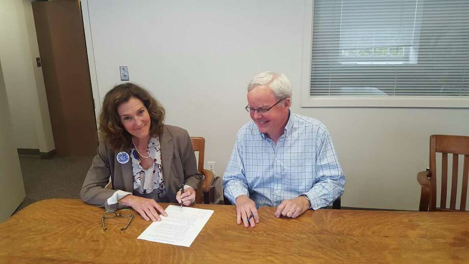Norwalk Federation of Teachers president Mary Yordon and Board of Education chairman Michael Lyons sign a tentative agreement that avoids teacher layoffs. Photo: Contributed Photo / Contributed