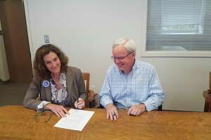 Norwalk Federation of Teachers president Mary Yordon and Board of Education chairman Michael Lyons sign a tentative agreement that avoids teacher layoffs.