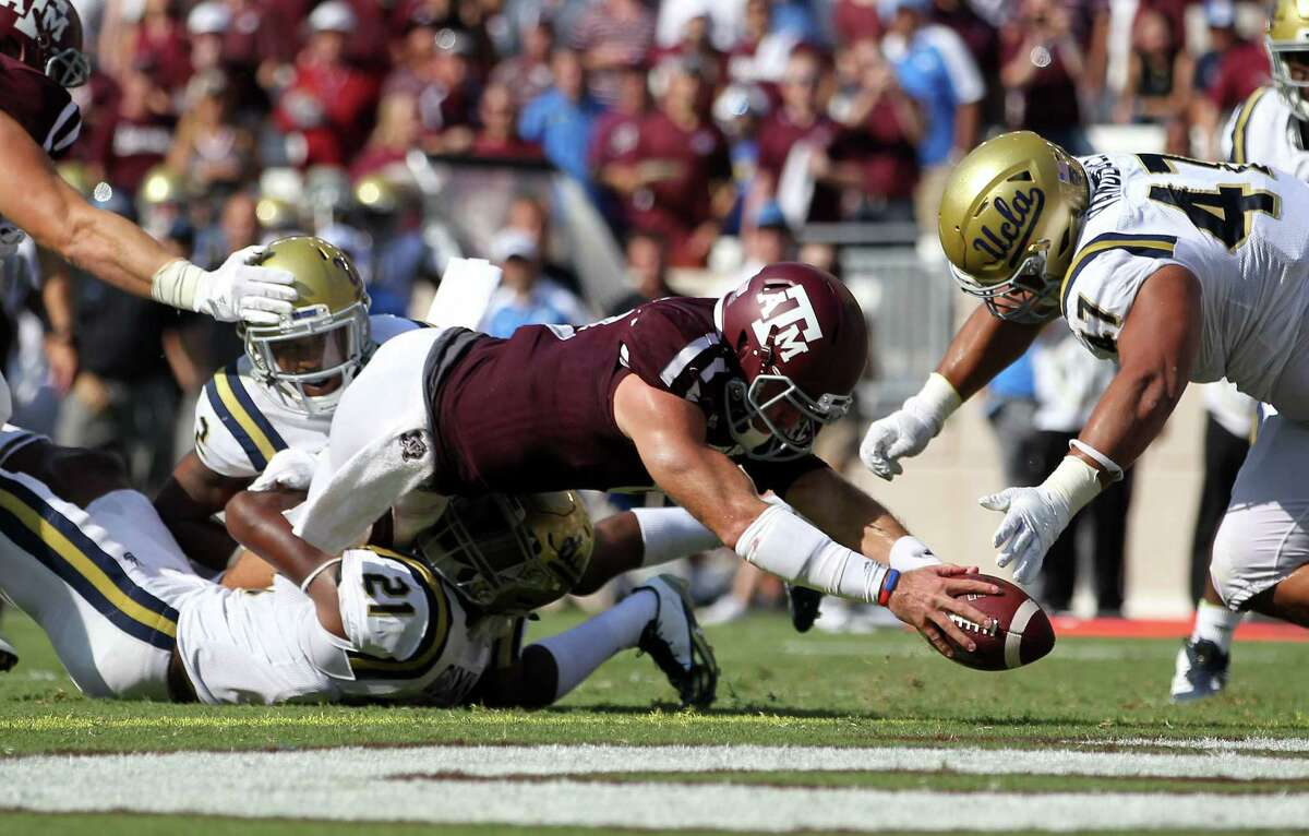 Texas A&M quarterback Trevor Knight (8) dives over the goal line for a touchdown as UCLA defensive back Tahaan Goodman (21) attempts to tackle him during the third quarter of an NCAA college football game Saturday, Sept. 3, 2016, in College Station, Texas. (AP Photo/Sam Craft)