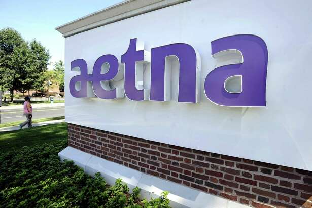 A pedestrian walks past a sign for Aetna Inc., at the company headquarters in Hartford, Conn. The insurer reported Friday that protected health information of about 522 Texas residents was available online for months.