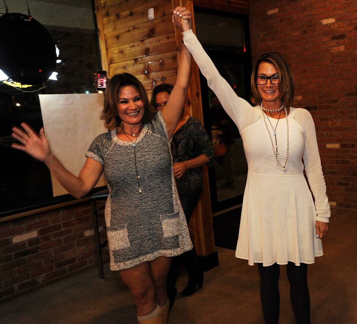 Republican Nicole Klarides-Ditria, left, enters American Pie and Pub with her arm raised by her sister, State House Minority Leader Themis Klarides, after winning the race for House District 105 in Seymour in November 2016.