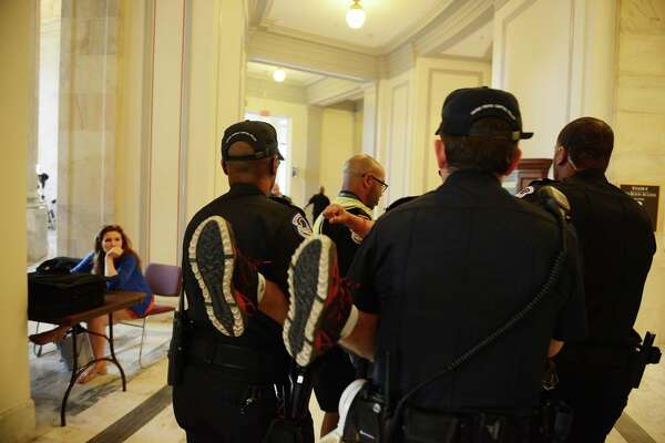 A demonstrator is taken away Thursday in the Russell Senate Office Building. As Majority Leader Mitch McConnell, R-Ky., was releasing the Senate's version of the health-care bill, people with disabilities staged a protest outside his office. Must credit: Photo by Astrid Riecken for The Washington Post