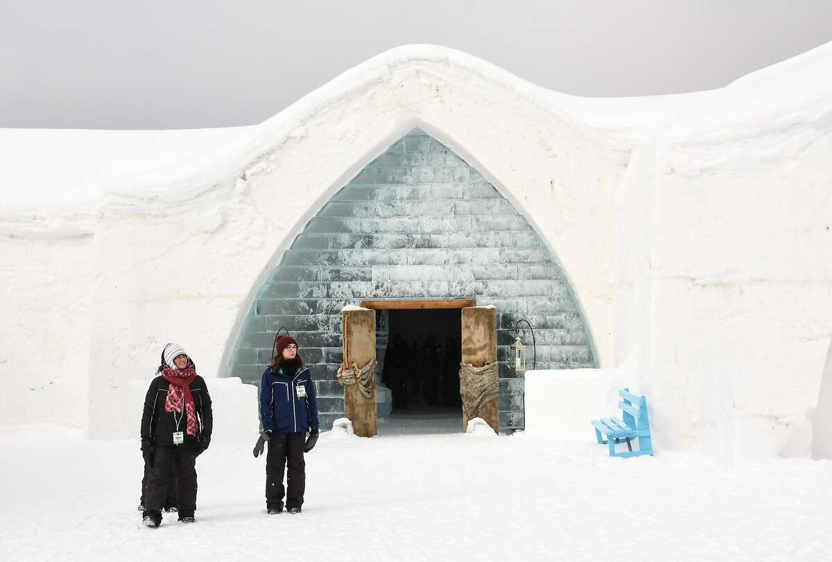 Staff stand outside the Ice Hotel (H�tel de Glace), a giant igloo complex in Quebec City, rebuilt annually out of 30,000 tons of snow and 500 tons of ice.