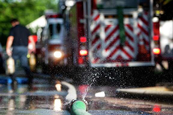 Water sprays from a hose as the Houston Fire Department crews battled a  blaze at an apartment complex on Upland near Sherwood Forest in 2013. (Chronicle File Photo)