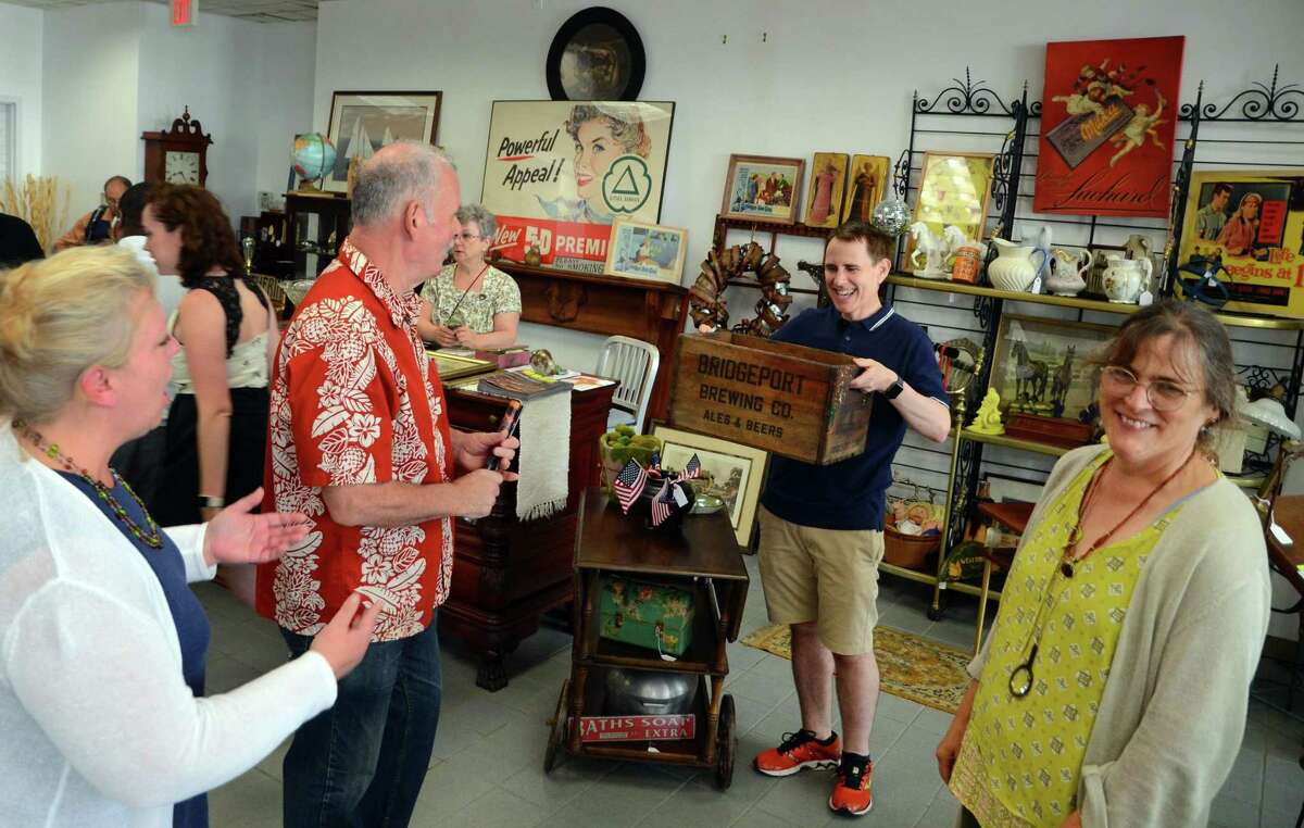 Above, John Brannelly, of Fairfield, shows off the Bridgeport Brewing Co. crate he found at the City Lights Vintage sale on Main Street in Bridgeport on Friday while City Lights Gallery Executive Director Suzanne Kachmar, at right, smiles. In photo at right, George Kachmar plays jazz guitar during the sale, which continues on Saturday from 10 a.m. to 4 p.m. Other stores taking part in the sale include The Bridgeport FLEA, 1127 Main St.; Orbitz Studios, 160 Fairfield Ave.; and Academy Books and Record, 305 Fairfield Ave.