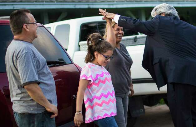 Celia Rodriguez, smiles as one of the attorneys of the family, David Medina, right, high-fives her  on front of the family's home in Houston, Friday, June 23, 2017. Photo: Marie D. De Jesus, Houston Chronicle / © 2017 Houston Chronicle