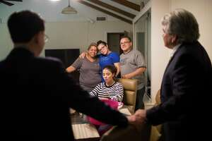 The Rodriguez family, Celia Rodriguez, Rebecca Rodriguez, 15, Karen Rodriguez, 18, and Juan Rodriguez, listen to their attorneys Juan Vasquez, left, and Juan Medina, right, while they share watermelons celebrating the 60-day reprieve granted by the U.S. government, Friday, June 23, 2017, in Houston.
