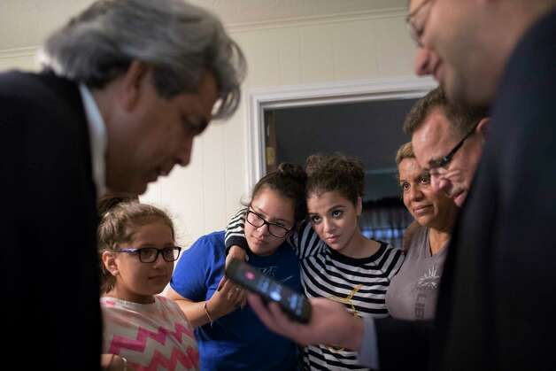 Juan Vazquez, right, holds a cellphone while David Calvillo, one of the three attorneys prays for the family after Juan Rodriguez was granted a 60-day reprieve by the U.S. government, Friday, June 23, 2017, in Houston. From left to right, Juan Medina, Kimberly Rodriguez, 10, Rebecca Rodriguez, 15, Karen Rodriguez, 18, Celia Rodriguez, Juan Rodriguez and Juan Vasquez. Photo: Marie D. De Jesus, Houston Chronicle / © 2017 Houston Chronicle