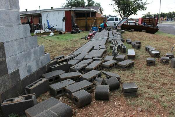 The concrete block fence was completely knocked down from the heavy winds that rolled through Midland Friday evening.