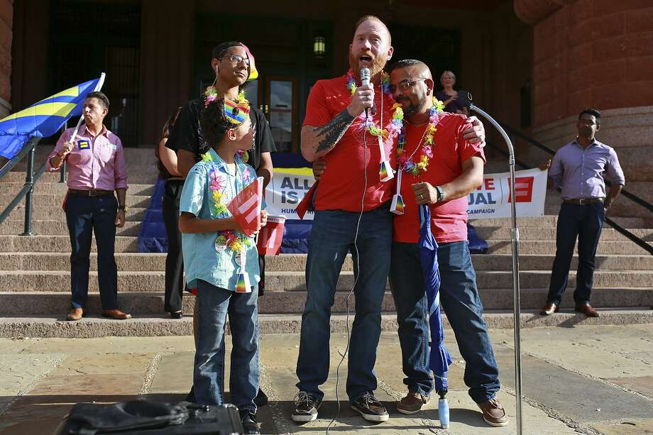Mark Sutherland-Trevino speaks to the crowd as he celebrates with his husband, Andres Sutherland-Trevino, right, after getting married earlier in the day, with two of their seven children including Marcus Sutherland-Trevino, 18, and Nathan Sutherland-Trevino, 9, during a rally to for the U.S. Supreme Court's decision to legalize gay marriage nationwide in front of the Bexar County Courthouse on Friday, June 26, 2015. Photo: Lisa Krantz, Staff / San Antonio Express-News / ©2015 San Antonio Express-News