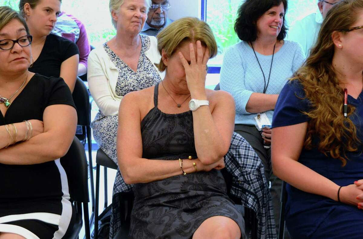 Fairfield resident Laura Karson covers her face during discussion of the effects of Medicaid cuts, at a forum with U.S. Sens. Chris Murphy, D-Conn., and Richard Blumenthal, D-Conn., at the Southwest Community Health Center in Bridgeport on Friday.
