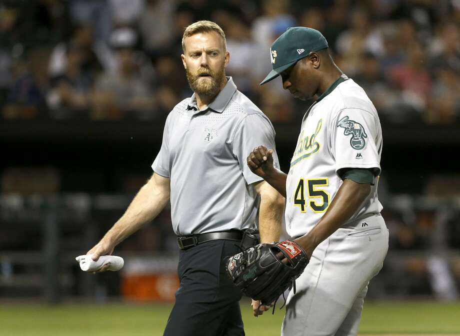 Oakland Athletics starter Jharel Cotton, right, leaves the game looking at his pitching thumb with a member of the medical staff during the sixth inning of a baseball game against the Chicago White Sox, Friday, June 23, 2017, in Chicago. (AP Photo/Charles Rex Arbogast) Photo: Charles Rex Arbogast, Associated Press