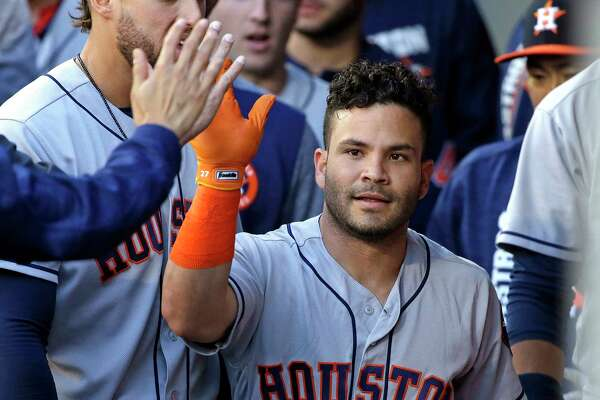 Houston Astros' Jose Altuve is congratulated on his home run against the Seattle Mariners during the first inning of a baseball game Friday, June 23, 2017, in Seattle. (AP Photo/Elaine Thompson)