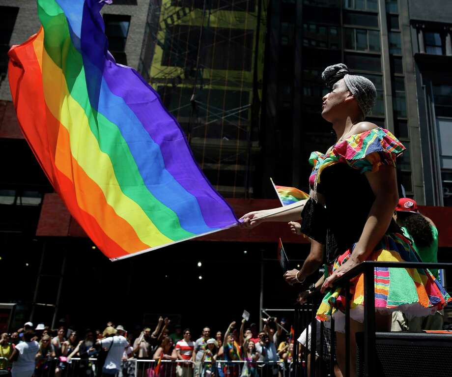 FILE - In this June 24, 2014 file photo, people on a float dance and wave flags during the annual pride parade in New York. The annual pride parade takes place on Sunday, June 25, 2017, amid protests by black and brown LGBT people saying increasingly corporate pride celebrations prioritize the experiences of gay white men and ignore the issues continuing to face black and brown LGBT people. (AP Photo/Seth Wenig, File) ORG XMIT: NYR402 Photo: Seth Wenig / Copyright 2017 The Associated Press. All rights reserved.