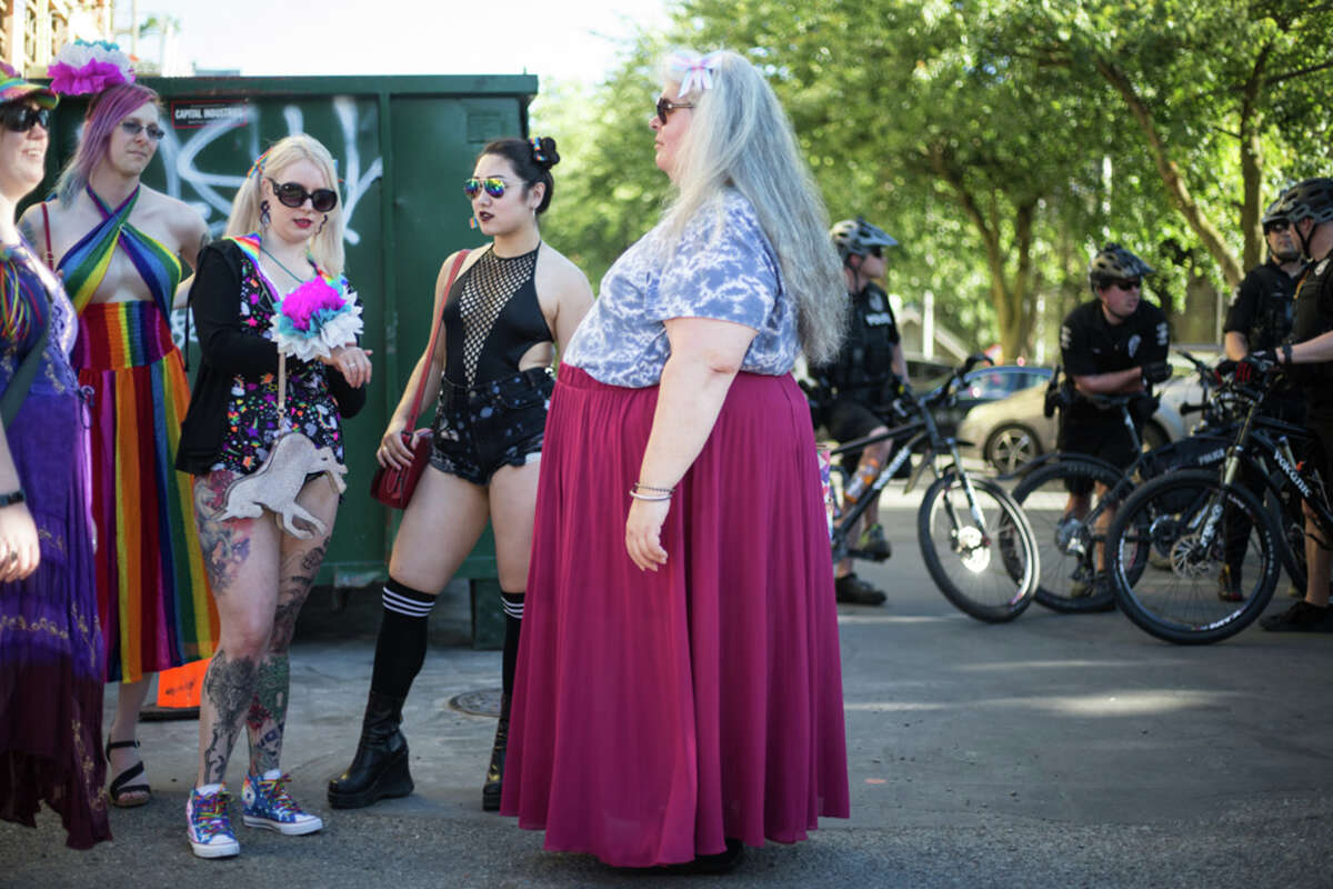 Trans Pride Seattle march participants visit as Seattle police stand guard.