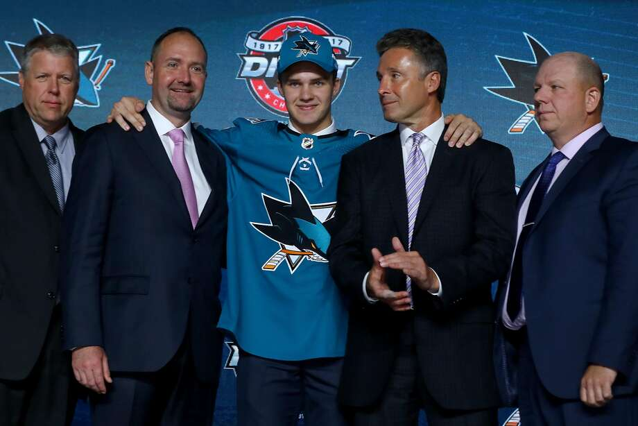 First-round pick Josh Norris puts his arms on the shoulders of Sharks head coach Peter DeBoer (second from left) and general manager Doug Wilson. Photo: Bruce Bennett, Getty Images