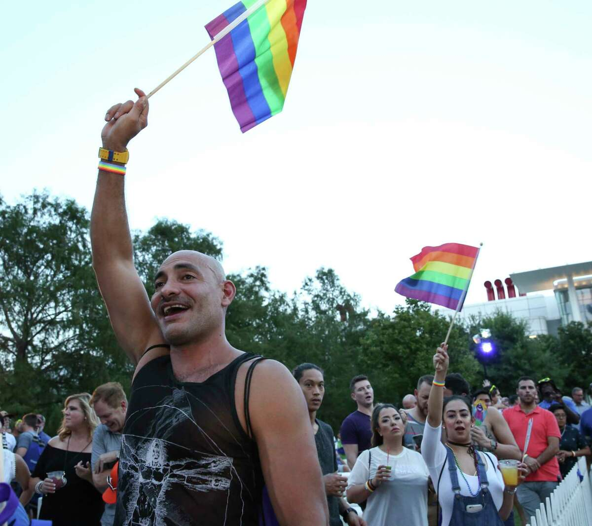 Mark Gongora waves a rainbow flag as he sings along at the seventh annual Rainbow on the Green musical event Friday at Discovery Green, part of the Pride Houston weekend celebrations.