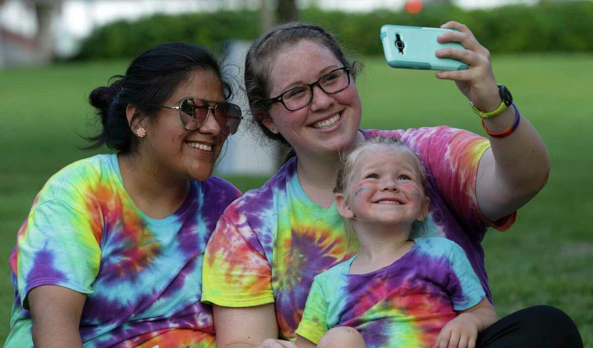 Anna Weaver, right, takes a selfie with her wife, Ruth, and 4-year-old son, Ezra, at the Rainbow on the Green musical event Friday. Saturday's pride parade will feature an HPD patrol unit emblazoned with rainbow decals.