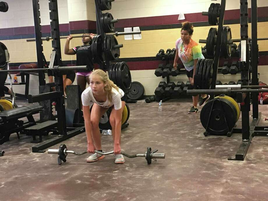 Sarah Green (center) does a dead lift, Britney Dixon (back left) does a push press, and Aeris Stallworth (back right) does a single leg touch at the Summer Creek Lady Bulldogs Speed and Strength camp on June 21. Photo: Elliott Lapin