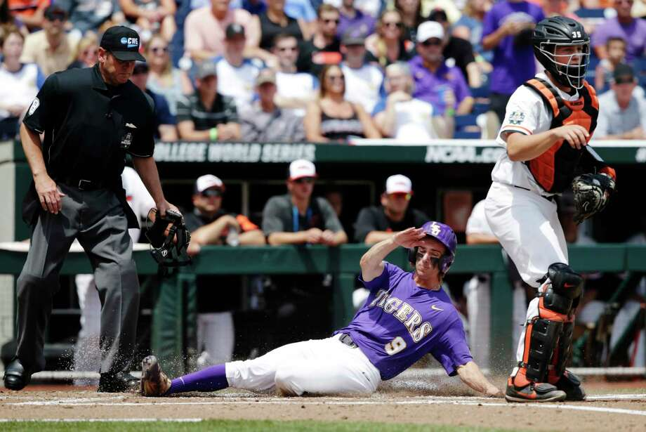 LSU's Zach Watson (9) slides past Oregon's catcher Adley Rutschman (35) to score on a sacrifice bunt by Beau Jordan during the second inning of an NCAA College World Series baseball game in Omaha, Neb., Friday, June 23, 2017. (AP Photo/Nati Harnik) ORG XMIT: NEFF105 Photo: Nati Harnik / Copyright 2017 The Associated Press. All rights reserved.