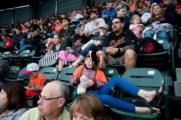Max Robinson, 10, lounges across seats while watching the Giants trail the Mets on Friday, June 23, 2017, in San Francisco.