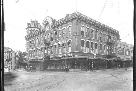 An oblique view of the George Dullnig Building, looking northwest at the corner of Alamo and Commerce Streets. The edge of the Royalty Coin/Clifford Building is visible on the far left. Black and white. Credit: Courtesy of the San Antonio Conservation Society Foundation, Raba Collection.