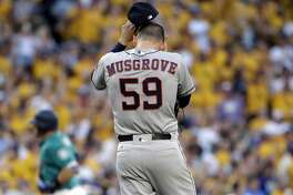 Houston Astros starting pitcher Joe Musgrove pulls off his cap as he waits for Seattle Mariners' Mike Zunino to round the bases on a three-run home run during the third inning of a baseball game Friday, June 23, 2017, in Seattle. (AP Photo/Elaine Thompson)