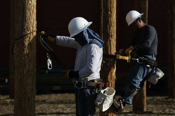 Students training to become electrical linemen attach themselves to poles during class at Los Angeles Trade-Technical College in Los Angeles on March 12, 2014.