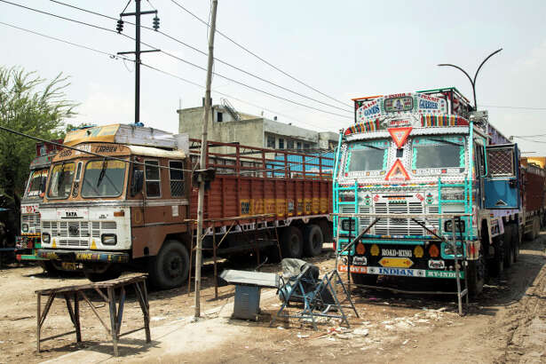 Trucks stand outside the Caravan Roadways Ltd. office at Sanjay Gandhi Transport Nagar in Delhi, India, on June 22, 2015.