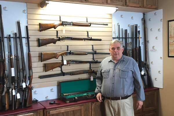 Terry Bast, owner of Goshen Guns, stands in front of a display of rare and antique shotguns. Goshen Guns recently opened at 214 South Main St. The shop offers a wide range of guns for both first-time gun owners to avid enthusiasts and collectors.