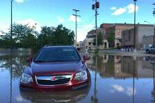 Rising waters from the Tittabawassee River hit downtown Midland as the river neared its projected crest of 31 feet on Saturday, June 24, 2017. A car is seen in the flood waters near Ann and Rodd streets.